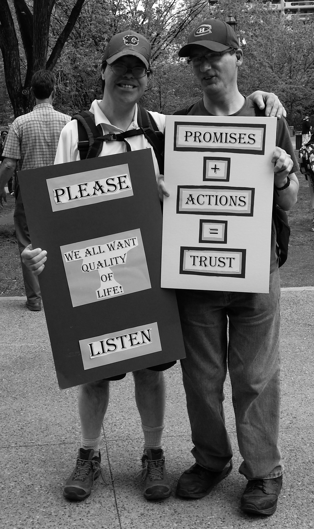 "Two protestors from the Disability Action group. Their signs say ""Please - We all Want Quality of Life. Listen"" and ""Promises + Action = Trust"""