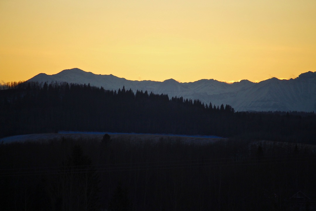 Golden sky at sunset with mountains in background of rolling hills.